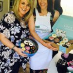 Suranne Jones and Sally Lindsay display cupcakes on sale at Surannes Cupcake Day party
